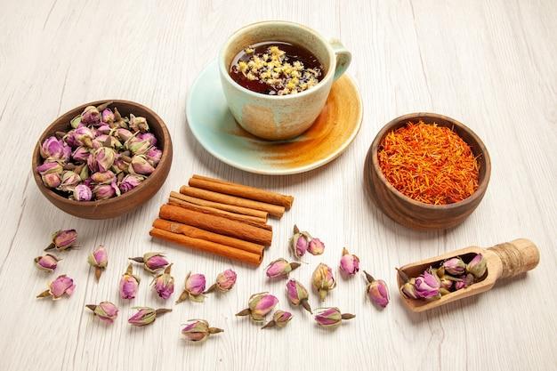 Tasse de thé avec des fleurs séchées et de la cannelle sur blanc