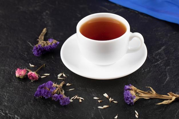 Une tasse de thé avec des fleurs séchées sur un tableau noir.