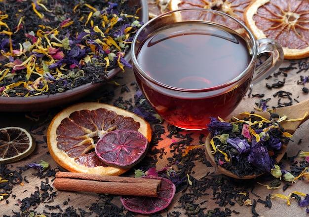 Tasse de thé frais et différentes variétés de feuilles de thé sur une table en bois. thé mélangé avec des pétales de fleurs et des agrumes séchés.