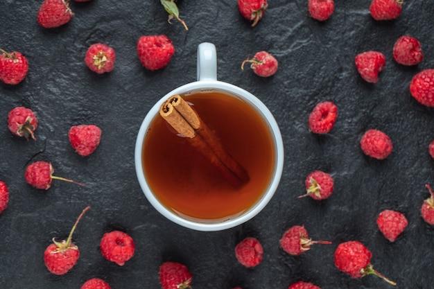 Tasse de thé et framboises fraîches sur tableau noir.