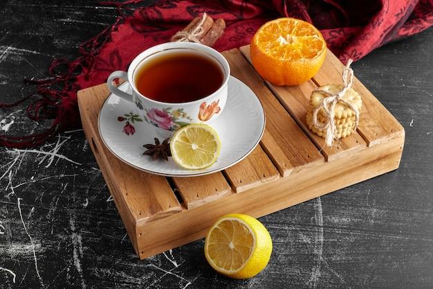 Une tasse de thé avec des fruits et des biscuits.