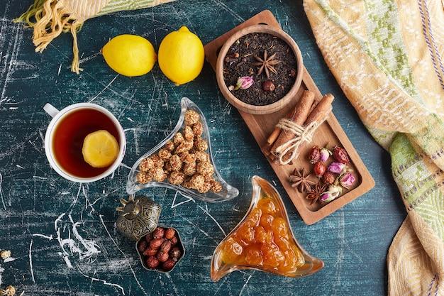 Une tasse de thé avec des fruits, des bonbons et des épices.