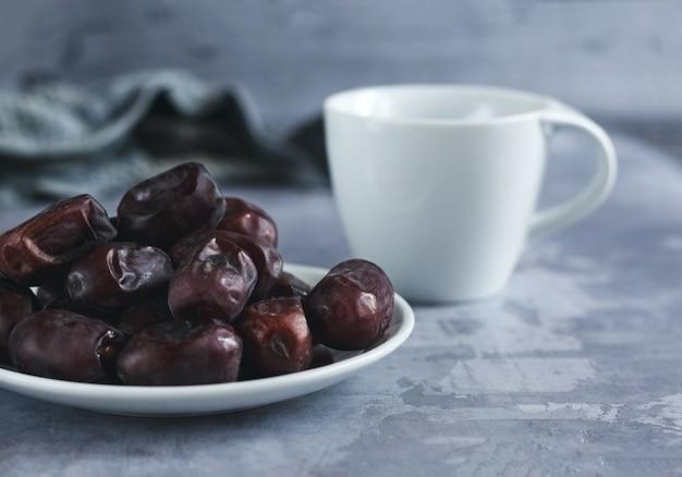 Tasse de thé et fruits secs sur fond de béton gris