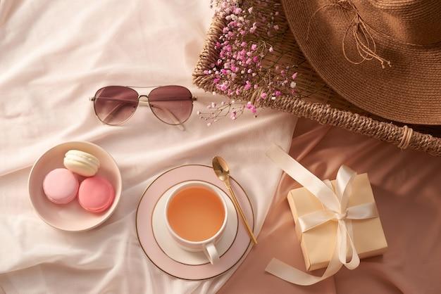 Tasse de thé, gâteau de macarons, boîte-cadeau, verres, chapeau et fleurs sur fond de tissu