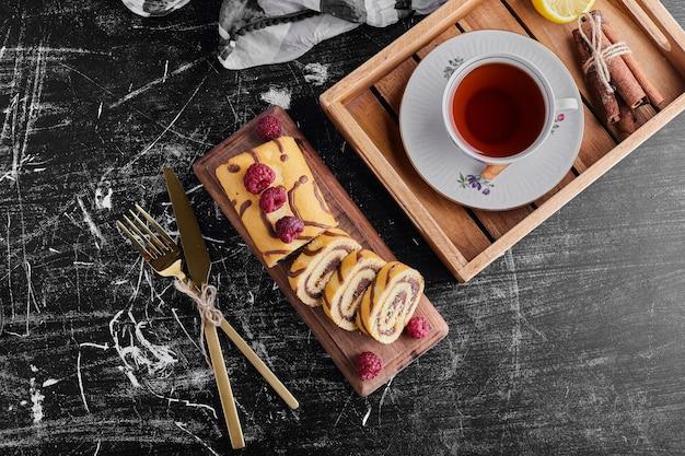 Une tasse de thé avec gâteau roulé, vue de dessus.