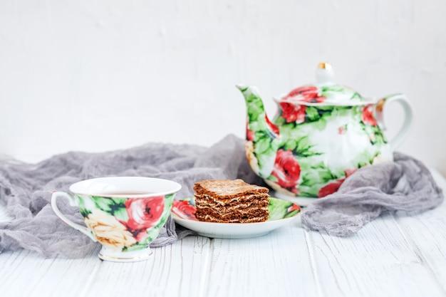 Tasse de thé et un gâteau sur une table en bois blanche.
