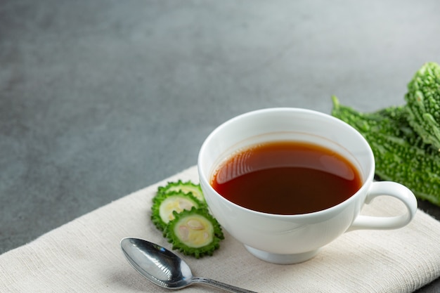 Une tasse de thé de gourde amère chaud avec place de gourde amère en tranches sur tissu blanc