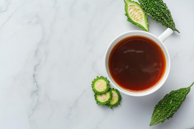 Une tasse de thé de gourde amère chaud avec des tranches de gourde amère crue sur un sol en marbre blanc