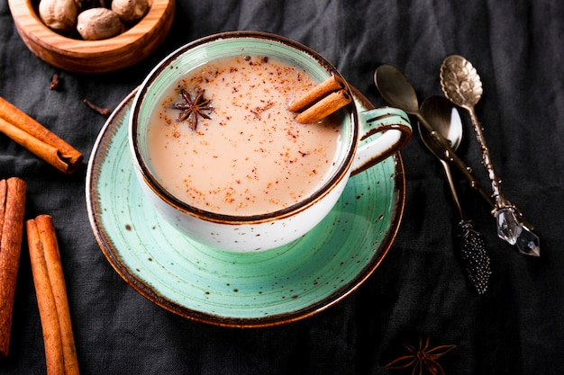 Tasse de thé indien traditionnel avec du lait et des épices sur une nappe en lin vue de dessus masala chai fermer