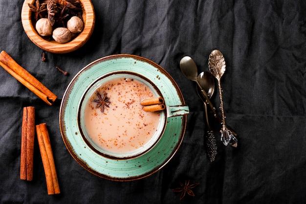 Tasse de thé indien traditionnel avec du lait et des épices sur une nappe en lin
