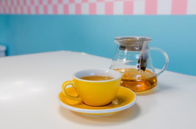 Tasse de thé jaune et théière en verre sur la table.