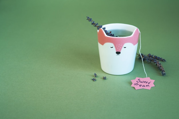 Une tasse de thé à la lavande pour faire de beaux rêves. fleurs de lavande sur fond de couleur mousse de terrarium