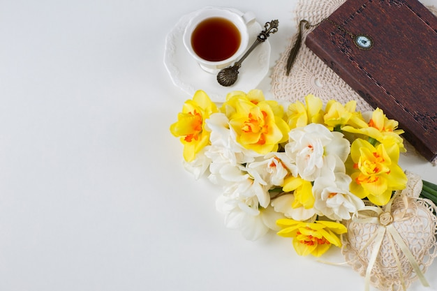 Une tasse de thé, un livre, un bouquet de jonquilles et un coeur de dentelle
