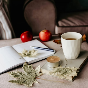 Tasse de thé avec un livre à l'intérieur avec une feuille d'automne