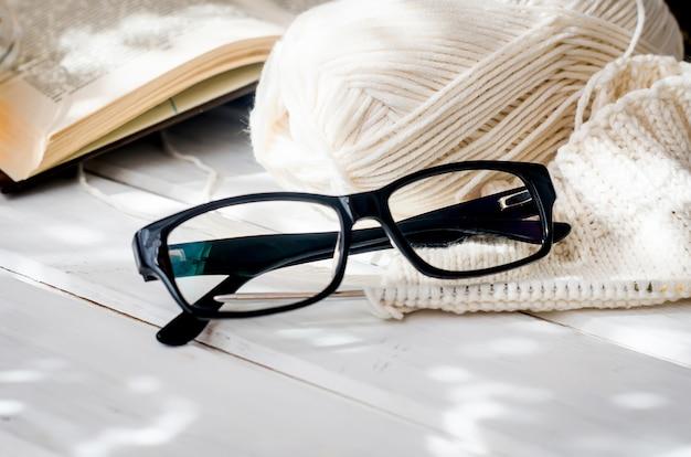 Tasse de thé, livre ouvert et lunettes avec ombre sumlight sur table en bois blanc. matinée douillette à la maison avec tricot, concept de confort et de chaleur,