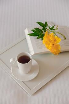 Tasse de thé avec un livre sur un plateau blanc avec une fleur jaune sur un lit blanc