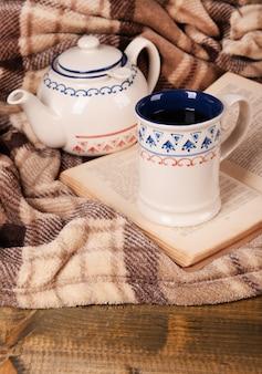 Tasse de thé avec livre sur table close-up