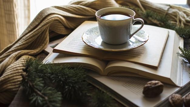 Tasse de thé sur des livres près de l'écharpe
