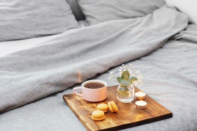Tasse de thé avec des macarons et des bougies sur un plateau en bois sur le lit