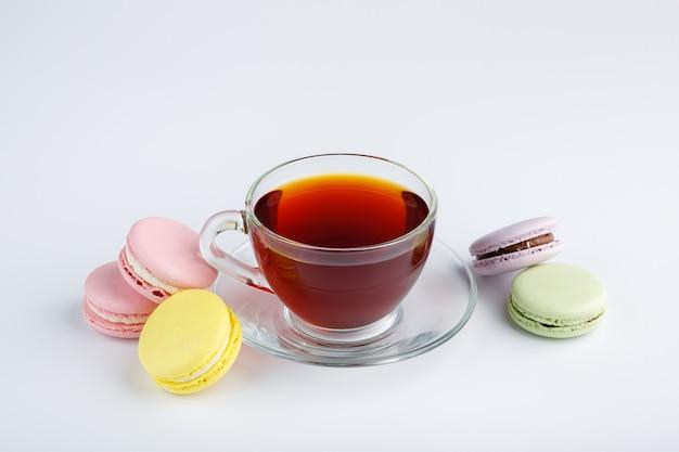 Tasse de thé et macarons colorés sur fond blanc