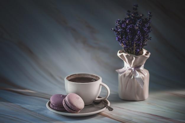 Tasse de thé avec des macarons à la lavande sur la texture. dessert français délicat. minimalisme, flou artistique, fond. tonique. bonjour .