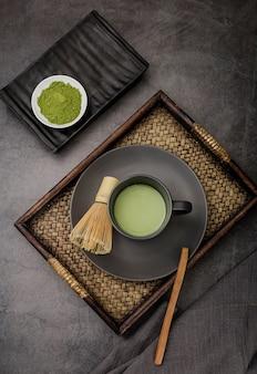 Tasse de thé matcha sur plateau avec fouet en bambou