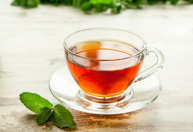 Tasse de thé à la menthe sur la table en bois de feuilles.
