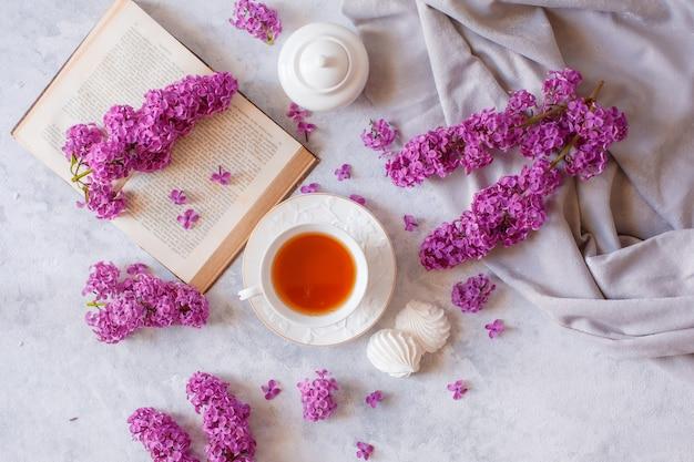 Une tasse de thé, meringue, branches de lilas en fleurs et un vieux livre