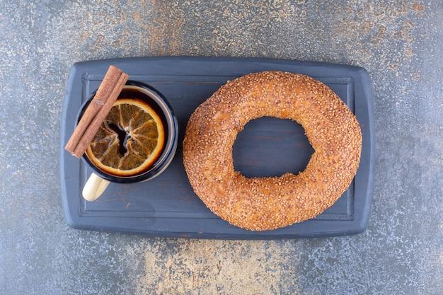 Tasse de thé en métal avec tranche de citron séché, bâton de cannelle et un bagel sur une planche sur une surface en marbre