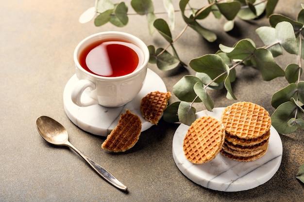 Tasse de thé avec mini-stroopwafel, biscuits sirop gaufres et brindilles d'eucalyptus sur surface légère