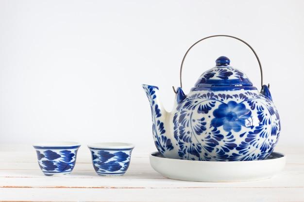Tasse à thé miniature avec théière sur planche de bois blanc, isolé, espace copie