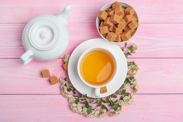 Tasse de thé avec des morceaux de sucre et des branches de fleurs sur la table en bois se bouchent