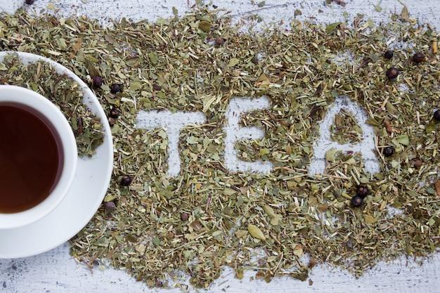 Tasse de thé avec le mot tea écrite en herbes sèches