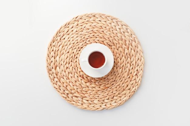 Tasse de thé sur napperon en fibre tressée ronde isolé sur blanc, vue de dessus.