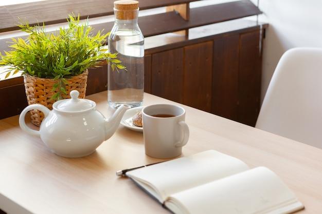 Tasse de thé noir chaud bouchent sur une table en bois