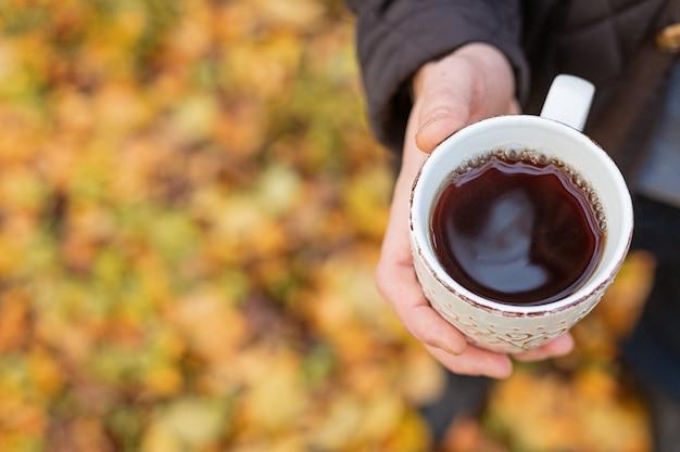 Tasse de thé noir chaud à la main en plein air. promenade dans la forêt d'automne espace copie - image