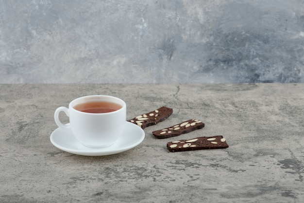 Tasse de thé noir avec des craquelins au cacao sur table en pierre.