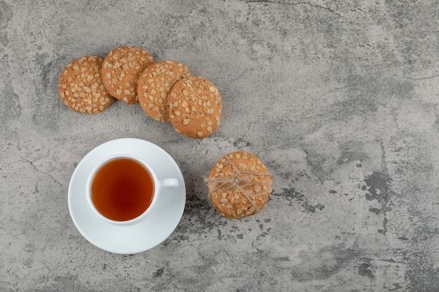 Tasse de thé noir avec de délicieux biscuits à l'avoine sur pierre.