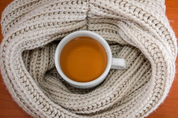 Tasse de thé noir enveloppée dans une écharpe tissée chaude, vue de dessus
