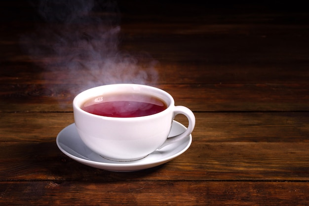 Une tasse de thé noir fraîchement moulu, une vapeur qui s'échappe, une douce lumière chaude
