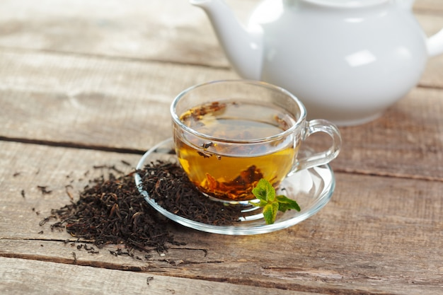 Tasse de thé noir à la menthe laisse sur une table en bois