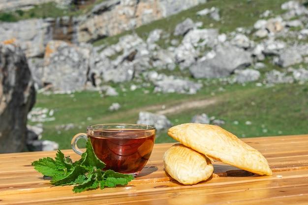 Tasse de thé noir avec des pâtisseries sucrées sur la nature