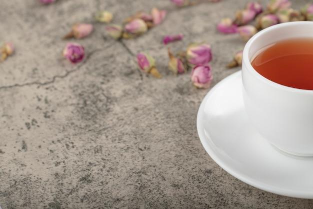 Tasse de thé noir avec des roses séchées sur la surface de la pierre.