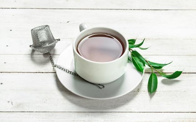 Tasse de thé noir sur une table en bois blanc
