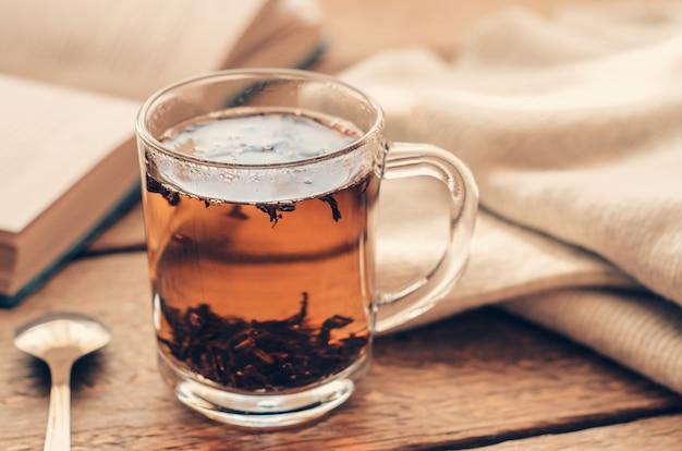 Une tasse de thé noir sur une table en bois avec un livre