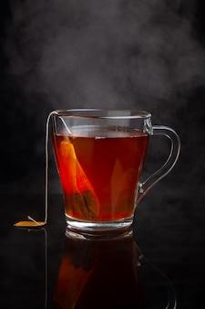 Tasse de thé noir avec de la vapeur sur un fond sombre