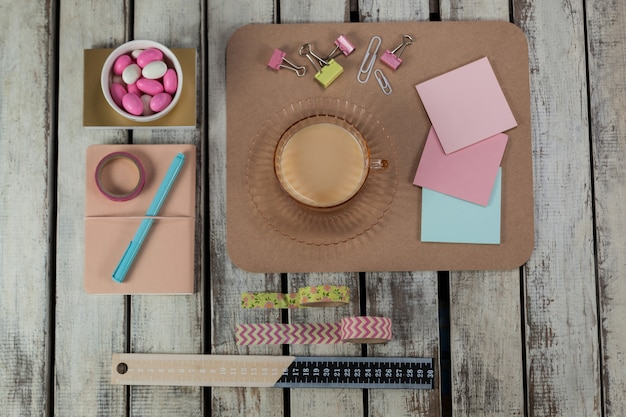 Tasse de thé, notes autocollantes, épingles à papier, trombones, ruban adhésif imprimé, règle et stylo