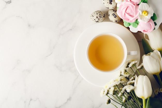 Tasse de thé avec des œufs et des fleurs
