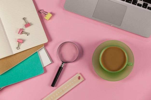 Tasse de thé, ordinateur portable, loupe, agendas, règle et trombones