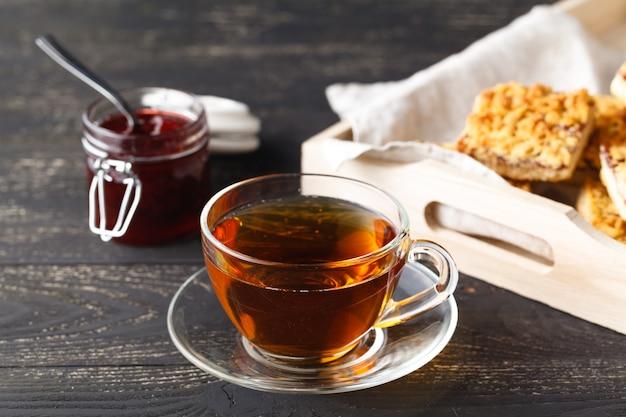 Tasse de thé et panier avec biscuits servis pour le petit déjeuner sur table en bois, table sombre